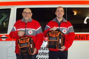 Die First-Responder Norbert Bach und Christoph Becker haben die neuen AED-Geräte erhalten. Foto: Guido Schultes, DRK Rhens